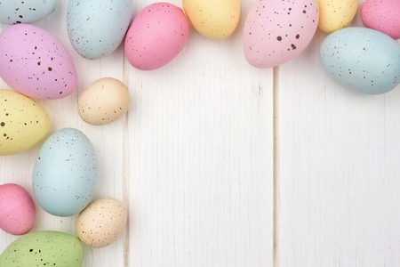 Pastel speckled Easter egg corner border against a white wood background Archivio Fotografico