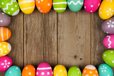 Colorful Easter egg frame against a rustic wood background