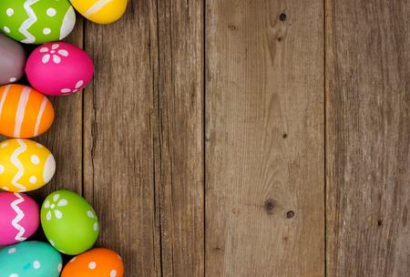 소박한 나무 배경에 다채로운 부활절 달걀 측면 테두리