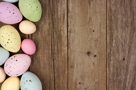 osterei: Pastell gesprenkelte Osterei Seitenrand gegen eine rustikale Holz Hintergrund