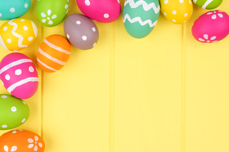 Colorful Easter egg corner border against a yellow wood background