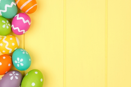 Colorful Easter egg side border against a yellow wood background Stockfoto
