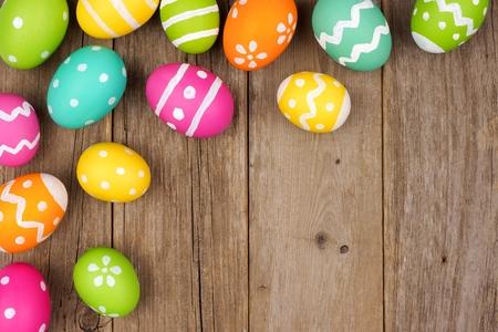 Colorful Easter egg corner border against a rustic wood background Banque d'images