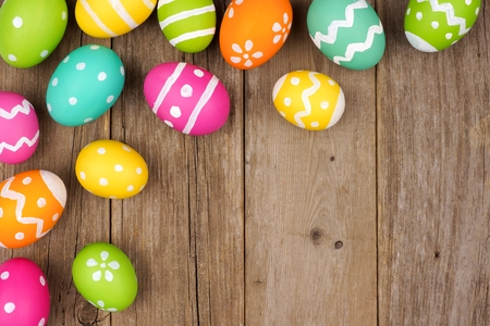 Colorful Easter egg corner border against a rustic wood background Stock Photo