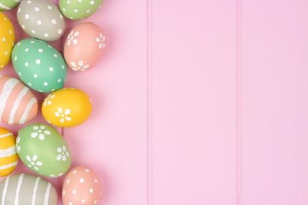파스텔 부활절 달걀 측면 테두리 분홍색 나무 배경