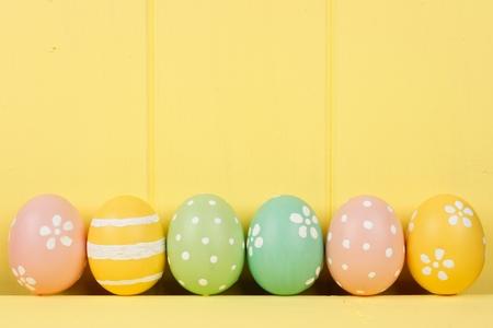 huevos de pascua: Fila de pintado a mano los huevos de Pascua sobre un fondo de madera de color amarillo Foto de archivo