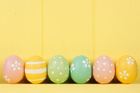 Row of hand painted Easter eggs over a yellow wooden background Stockfoto