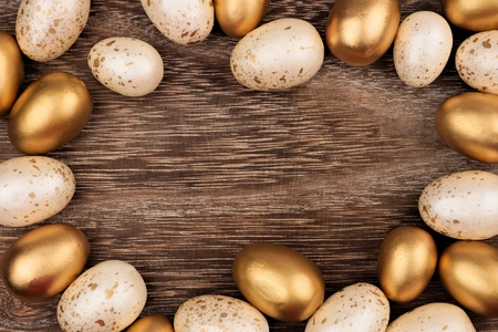 White and gold Easter egg frame against a rustic wood background