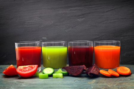 marchew: Four glasses of healthy vegetable juice with scattered vegetables and a dark slate background