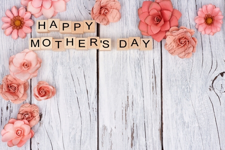 Happy Mothers Day wooden blocks with rustic paper flower top corner border on a white wood background