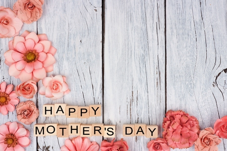 Happy Mothers Day wooden blocks with rustic paper flower bottom corner border on a white wood background