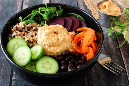 Healthy salad bowl with hummus, beans, wild rice, beets, carrots, cucumbers and pea shoots.