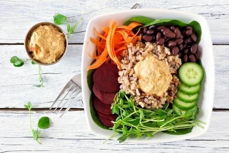 フムス、豆、ワイルド ライス、ビート、ニンジン、キュウリ、エンドウ豆が付いている健康栄養ボールを撃ちます。白い木製の背景の平面図です。