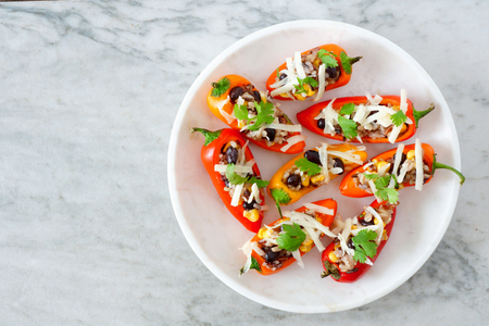 Plate of healthy stuffed mini peppers with wild rice, cheese, beans, corn and cilantro. Top view on a light background. Stock Photo