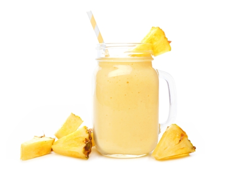 Pineapple smoothie in a mason jar with straw and scattered fruit isolated on a white background