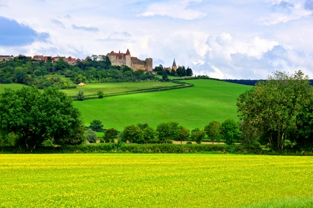 Castle and village of Chateauneuf en Auxois behind rolling green hills, Burgundy, France