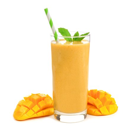 Healthy mango smoothie in a glass with mint and straw isolated on white