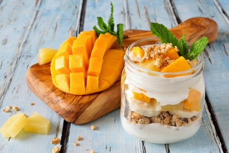 Tropical mango and pineapple parfait in a mason jar on a rustic blue wood background Stockfoto