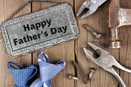 Happy Fathers Day greeting on metal sign with tools and ties on a wooden background