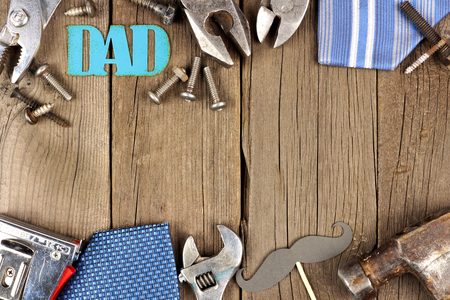 Metallic DAD sign with double border of tools and ties on a wooden background