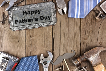 Happy Fathers Day message on a metal sign with double border of tools and ties on a wooden background Stock Photo