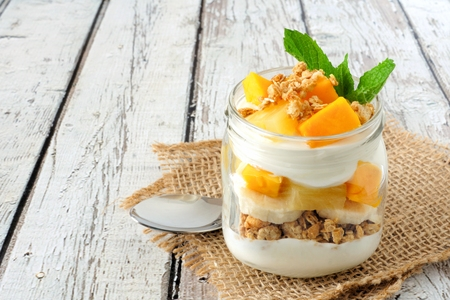 Tropical mango and pineapple parfait in a mason jar on a rustic white wood background Фото со стока