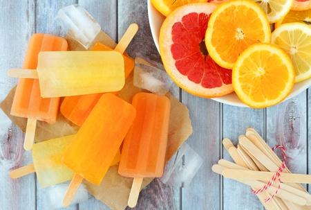 Orange, lemon and grapefruit ice pops, overhead scene on a rustic wood background Standard-Bild