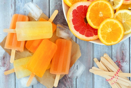 Oranje, citroen en grapefruit ijs knalt, overhead scène op een rustieke houten achtergrond