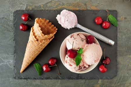 Bowl of cherry chocolate ice cream, above scene with cones and scoops on a slate background