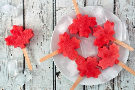 Canadian maple leaf watermelon pops on a plate against a rustic old white wood background Stock Photo