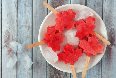 Canadian maple leaf watermelon pops on a white plate against a rustic old wood background