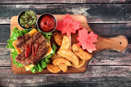 Canada Day picnic scene with maple leaf shaped hamburger and watermelon on a paddle board over rustic wood