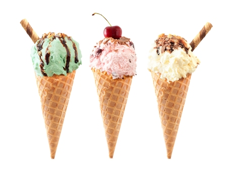 Pistachio, cherry and vanilla ice cream with topping in waffle cones isolated on a white background