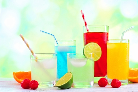 Group of colorful summer drinks against a green outdoors background