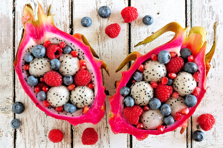 Colorful dragon fruit salads with raspberries and blueberries over a white wood background