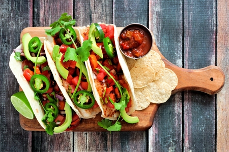 Spicy fish tacos with watermelon salsa and avocados on a paddle board against a rustic wood background