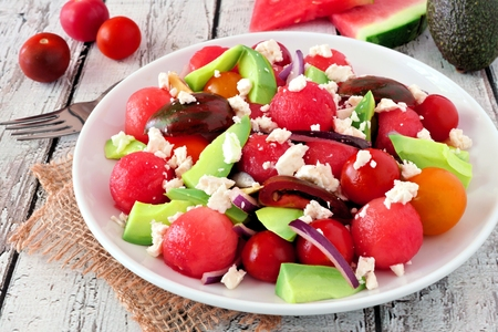 Summer salad with watermelon, avocado, tomatoes and feta cheese, close up in a white plate