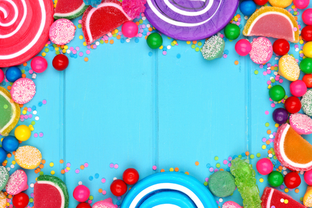 Frame of assorted colorful candies against a blue wood background