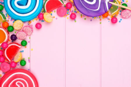 gumballs: Top corner border of assorted colorful candies against a pink wood background