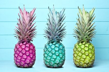 Pineapples of different color hues on a pastel blue wooden background