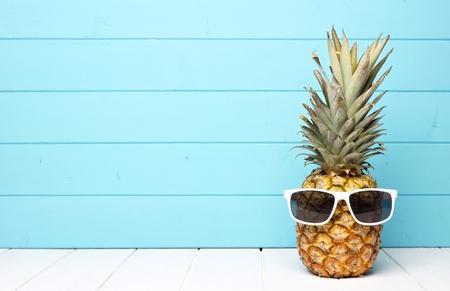 Ananas anatra con occhiali da sole contro uno sfondo blu in legno Archivio Fotografico - 81169473