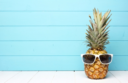 Hipster pineapple with sunglasses against a blue wooden background