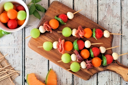 Summer fruit skewers with melon, cheese and prosciutto on a wood serving board, above scene on white wood
