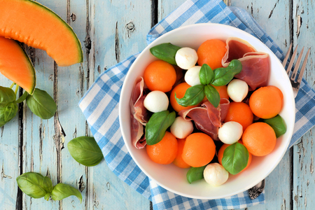 Summer salad with cantaloupe, mozzarella, prosciutto and basil, above scene on a blue wood background Stock Photo