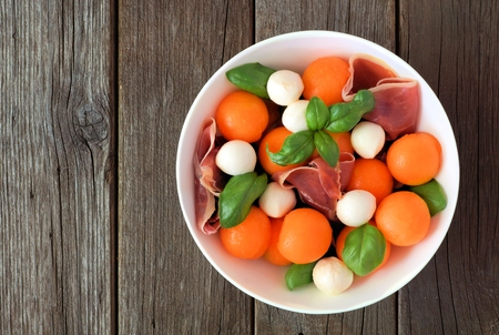 Salad with cantaloupe, mozzarella, prosciutto and basil, top view on a rustic wood background