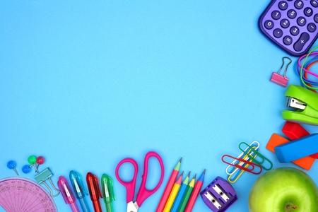 Materiale scolastico di basso angolo di frontiera contro uno sfondo di carta blu Archivio Fotografico - 82239629
