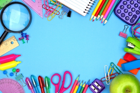 School supplies frame against a blue paper background