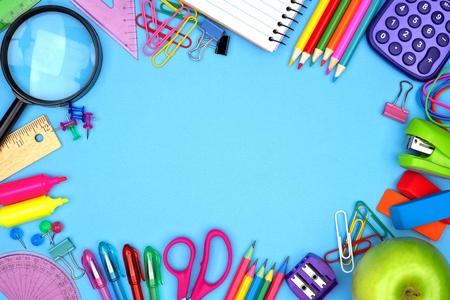 Schulbedarf Rahmen gegen einen blauen Papierhintergrund