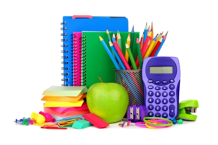 Books and a colorful group of school supplies isolated on a white background