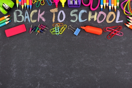 School supplies top border with Back To School written in colorful chalk against a chalkboard background Stockfoto